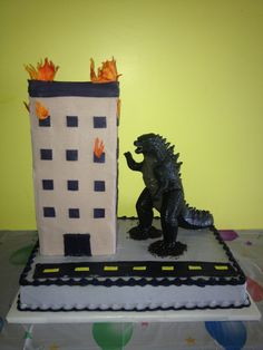 """Godzilla Cake: stacked 6"""" square cakes iced with buttercream icing with rolled fondant windows and flames. Godzilla toy standing in Oreo cookie crumbs."""