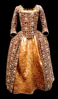 Robe à l'anglaise, England, 1770-1779. Hand block printed glazed cotton 'dark ground chintz', with a design of floral stripes on dark brown ground, linen lining; petticoat: gold coloured quilted silk satin.