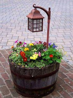 """This decorative half whiskey barrel planter looks amazing with the multi-colored flowers and the rustic, lantern. Southern Patio has a line of 15.5"""" Resin Whiskey Barrels in Kentucky Walnut that would be perfect for this creative outdoor project! http://www.southernpatio.com/products/planters/hdr-007197-15-5-hdr-whiskey-barrel-kentucky-walnut/ #containergardening #decorativeplanter #resinplanter"""