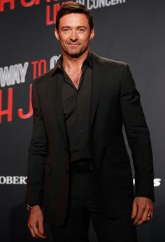 Hugh Jackman sports a black Dolce & Gabbana suit, worn sans tie with a black dress shirt.