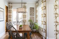 Chic cottage dining room boasts a scalloped linen pendant illuminating a farmhouse dining table lined with gray windsor dining chairs surrounded by windows and doors dressed in white and gold feather print curtains.