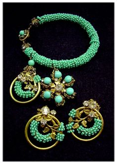 Haskell Ultra-Charming Gilt & Aqua Charm Bracelet & Earrings    Our circa '50s set showcases huge gilt and aqua floral charms on a bracelet meticulously hand-beaded with aqua seed beeds, plus earrings that look like one of the charms.    Haskell charm bracelets are scarce; one dating to the '50s is a real treasure find. And how can you resist something this pretty?    The bracelet is a flexible rolled band completely covered with glass seed beads in a vivid aqua blue. Closest to one end…