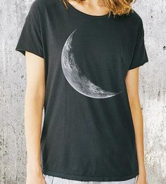 A silvery crescent moon graces the front of this vintage-washed t-shirt. It's printed in white ink, the details of the lunar surface crisp and clear in white ink against the faded black fabric.