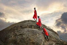 David Lazar - The Ascent - Three Masais help each other climb to the top of a boulder overlooking the plains of the Masai Mara, Kenya.
