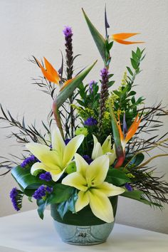 Birds of Paradise and yellow lilies in this tropical flower arrangement by Willow Branch Florist of Riverside