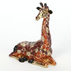 A shimmering orange and red mosaic, encrusted with clear crystals makes this Giraffe Trinket Box a dazzling jewel by itself. But a gentle lift of the elongated…