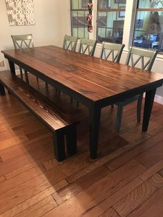 "James+James 9' x42"" Farmhouse Table with a traditional top stained in Vintage Dark Walnut and a painted black base and tapered legs. Pictured with matching Farmhouse Bench.  Large customizable rustic dining table green dining chairs hardwood floor solid wood furniture"