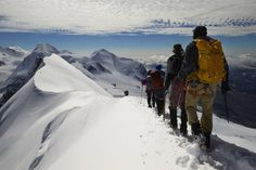 These Alpine climbers are straddling the crest of the Breithorn which marks the boundary between Switzerland and Italy