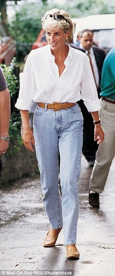 Princess Diana wears a baggy white shirt tucked into jeans during a visit to promote the Red Cross landmines campaign in Bosnia