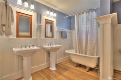 """master bath. like wainscote and love """"plate rail"""" shelf, but not quite so tall. Dual old style med cabinets nice, and divider btwn tub and toilet area. 1916 Wallingford (bath appears to be new, but well done except ugly sinks)"""