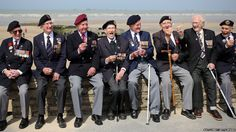 Normandy Veterans enjoy lollipops as they sit on a wall in front of the beach at Arromanches