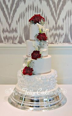 An all white cake with sugar ruffles on the base tier and finished with silver ribbon.  The fresh flowers, red carnations, calla lilies and silver gyp were arranged by the bride's florist. Delivered to the very beautiful Bibury Court in the Cotswolds.
