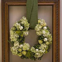 Xmas wreath hanging with a thick ribbon. Love the variety of flowers and plants incorporated throughout with a touch of ornaments through out.