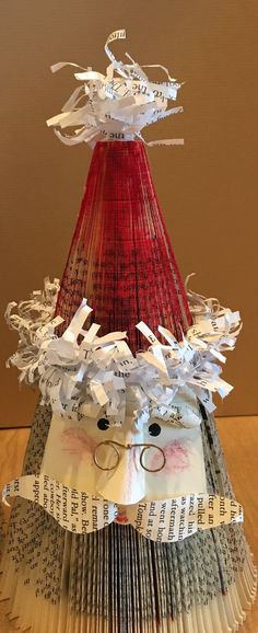 "These stacked BOOK PAGE SANTAS made from fanned book pages are great for stand alone, centerpieces, shelves, and GIFTS. Ships and stores flat for protection and convenience. SANTAS are stacked separate sections. Can be ""fluffed"" by pinching together open sections at the center and or, Folded Book Art, Book Folding, Christmas Projects, Holiday Crafts, Holiday Decor, Upcycled Crafts, Diy Crafts, Christmas Tree And Santa, Book Page Crafts"