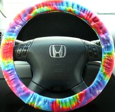 "Brand new, homemade, fleece fabric tie-dye retro hippie multi-color print steering wheel cover. All covers come with non-slip grippers sewn inside and will fit any standard sized wheel (14"" - 16""), but can be custom made for a larger or smaller wheel. Hand wash in cold water recommended, but this cover can be tossed in the washer and dryer too."