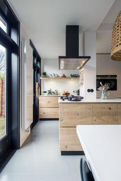 Cuisine chic avec meuble en bois. L'entourage des baies vitrées noir relève la décoration...