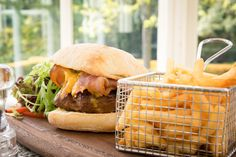 Matfen Homemade Burger with Bacon and Harrogate Blue  Cheese Served on Ciabatta with Fries.  Lunch time idea. Bar meal. Bar food.