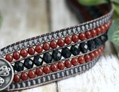 One Only, made and ready to go! Gorgeous sparkly denim blue crystals surrounded by rows of matte denim and translucent carnelian red, hand stitched onto distressed grey leather. This beaded leather cuff makes stacking easy, 5 rows of beads and leather in one easy to fasten bracelet. Antique silver finished 1 metal button may be worn above or under your wrist. Cuff Measurements; 1 1/2 wide. Fits a 6 1/4 wrist comfortably and snug on a 6 1/2 wrist. Questions about sizing, please convo me :)…