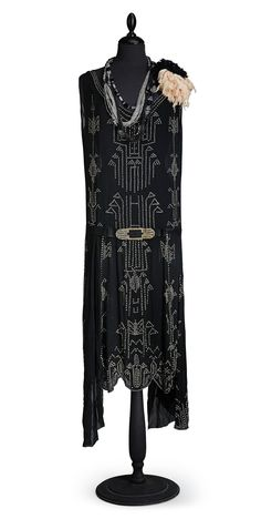 ~Evening gown, 1920s~ black chiffon with decoration of foliated glass stones in geometric patterns, belts of black moire, metal buckle with decoration of black and foiled glass stones, marked Biby 25., Asymmetrical cut, comes with 2 necklace in black and transparent glass; glass stones missing PROVENANCE: Biby Fideikommiss, Gillberga parish, Södermanland County