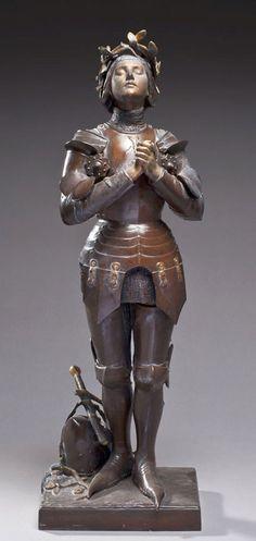 """Statuette en régule patinée, figurant Jeanne d'Arc, en prière. Portant une signature : """" MERCIÉ """""""