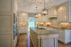 White cabinets that go to the ceiling add extra storage for all of your holiday dishes. Lighter the paint color, larger the kitchen looks.  Lighting underneath the cabinets brightens up the granite counter tops.