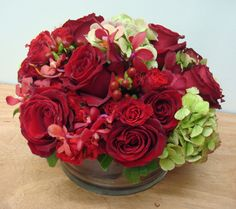 This is an arrangement of red roses, red mokara orchids and green hydrangea.  See our entire selection at www.starflor.com.  To purchase any of our floral selections, as gifts or décor, please call us at 800.520.8999 or visit our e-commerce portal at www.Starbrightnyc.com. This composition of flowers is generally available for same day delivery in New York City (NYC). RO081