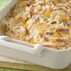 Two kinds of cheese, sour cream and green onions make these scalloped potatoes with ham a quick, creamy side dish for a large crowd.