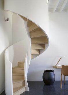 Moderne Wendeltreppe mit weißem Gelände und Treppenstufen in hellem Holz.