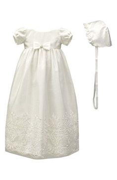 A long, heirloom-quality christening gown is detailed with a bow embellishment at the waist and exquisite lace at the hem. A matching bonnet with satin ruffles completes the precious set.