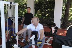 Russian President Vladimir Putin (R) and Prime Minister Dmitry Medvedev exercise in a gym at the Bocharov Ruchei state residence in Sochi, Russia