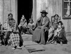 Creeping Bear with his wife, Boy Head and their five children, in front of their home at Seger Colony in Oklahoma Territory - Southern Arapaho - 1900: