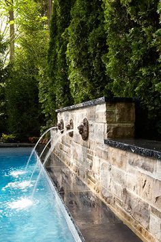 fountains into pool, stone wall, evergreens | best stuff