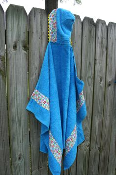 Turquoise hooded towel with flower details.