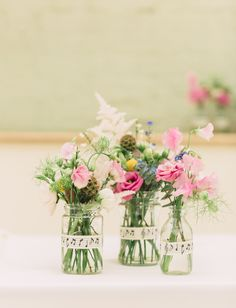 Glass jars wrapped in music note ribbon and filled with pink flower stems - Image by Charli Photography - Lusan Mandongus Lace Dress for a rustic wedding in barn with musical theme and pastel colour scheme.