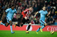 Connor Wickham of Sunderland splits the Manchester City defence to score the opening goal during the Barclays Premier League match between Sunderland and Manchester City at The Stadium of Light on December 3, 2014 in Sunderland, England.