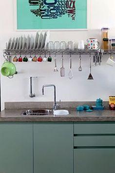 (1) Para deixar livre a bancada desta cozinha, o designer de interiores Marcel Steiner instalou PRATELEIRAS METÁLICAS (Sistema de parede), DA METAL STOCK (http://www.metalstock.com.br/). Além de servirem de escorredor de pratos, elas também guardam potes de mantimentos e utensílios presos por ganchos. (2) Em vez de usar pedras, Marcel preferiu executar a bancada de concreto.: