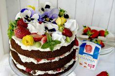 Chiffon cake al cioccolato con panna e fragole con fiori e meringhe
