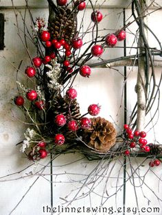 CUSTOM ORDER FOR NANCY OTTE  (9)  A rustic window frame is constructed of white birch branches, and intertwined with curling twigs. It is adorned with frosted crimson berries and dried pine cones. The star-like blooms of dried ivory German statice arch gracefully like tiny constellations. A faux woodland bird perches for a moment on the window ledge. The frame measures 15 x 15, and the outermost measurement, from splaying branch tip to splaying branch tip is approximately 21 wide x 21 high…