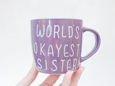 WORLDS OKAYEST SISTER Handpainted Coffee Mug in Purple  For guys, it can be hard to express your love toward your sister since you were born to