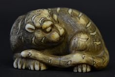 A Japanese Ivory Panther Netsuke, Edo Period, the recumbent figure of a panther with finely incised fur, with hairline cracks, appx. 1 3/4 in. W.Similar Netsuke sold at Christie's - London, May 16, 2012, for 3,500 British Pounds.