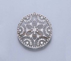A BELLE EPOQUE DIAMOND BROOCH  Of circular form, the filigree plaque decorated with a central old mine-cut diamond rosette, to the diamond collet trim and scalloped motifs, (together with a fine-link chain, not illustrated), circa 1910