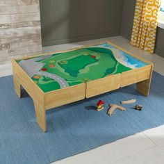 This wooden play table is just what little ones need to engage in fun imaginative play. It features an expansive double-sided play board for arts and crafts or a fun landscape to build their favorite train track combination.  Built in storage compartment helps keep rooms tidy after play time.