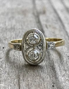 This is THE sweetest ring. Perfect for a promise ring, anniversary or just because! Two old European cut diamonds sit atop one another in bezel settings. Each weighs approximately .11 Ct each and G-H in color, SI1 clarity. 4 rose cut diamonds accent this piece and the entire oval shaped face has well preserved mill grain details. Its easy to wear and very sparkly! Size: 7  Measurements: the face of the ring measures 11.1 mm x 7.6 mm with a rise off of the finger of 4mm  Markings: none…