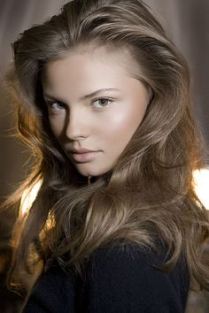 Voluminous brunette hair with glowing highlighted skin.