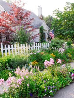 Add curb appeal, brighten your entryway, and make your home more inviting with a beautiful front yard flower garden. Check out this collection of front yard flower garden ideas. White Picket Fence, Picket Fences, Picket Fence Garden, White Fence, Pool Fence, Garden Cottage, Cottage Front Yard, Cozy Cottage, Cottage Style