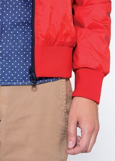 A denim shirt characterized by a vintage wash and white polka-dot print, under a red nylon jacket and a pair of beige shorts. SUN68 Man SS15 #rainjacket #SUN68 #SS15