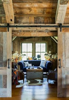 Navy blue sofa in an all-wood cabin living room with sliding living room doors. Refreshing in its simplicity, rustic style highlights natural beauty and a rugged, resilient spirit as reflected in these rustic living room designs.