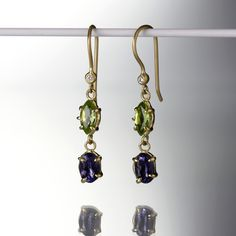 "These Anne Sportun earrings are some kind of wonderful! The oval iolite and marquis peridot are set in 18K yellow gold claw bezels, and dangle below a  sparkling bezel set diamond. These simplistic beauties get their gorgeous movement  from the perfectly rendered ear wires they hang below. Talk about decadent layers!<br><br>Peridot measures 7mm x 3.5mm <br>Iolite measures 6mm x 4mm <br>Diamond = .01cttw diamond<br>Earrings measure 1.25"" in length"