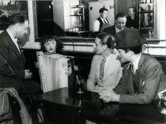 Vers 1936. Edith Piaf chantant dans un café, accompagné de son accordéoniste Buel, de Raymond Asso et de Marcel Montanon. Par Jean-Gabriel SERUZIER. Source: http://natifs50-graulhet.wifeo.com/article-85596-au-bistrot-breves-de-comptoir-av.html