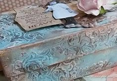 Cover box with gesso and patterned paper. Use stencil with texture paste, then distress paint over the top to add color.